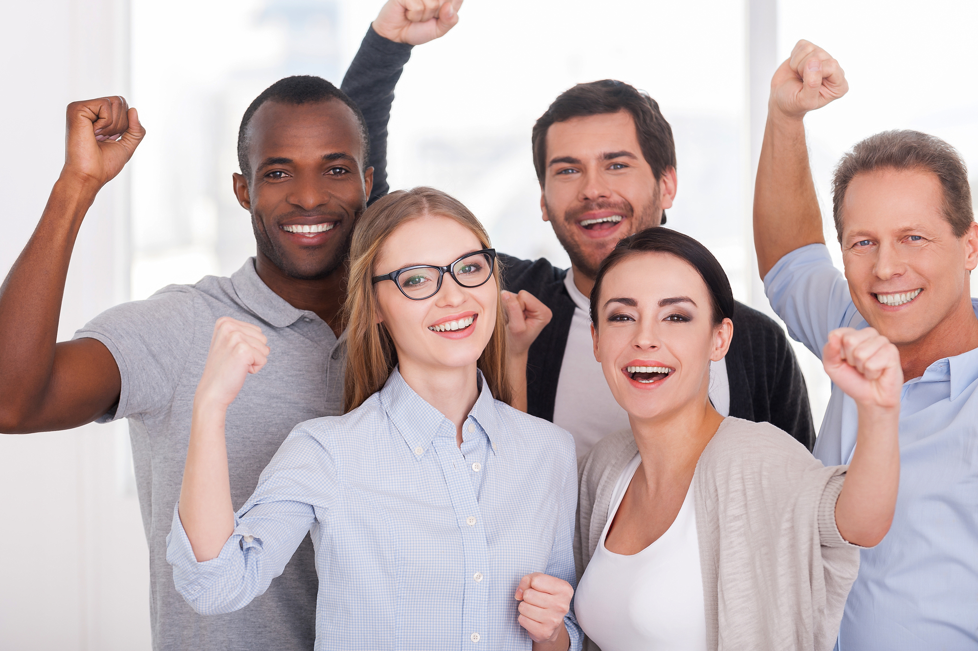Happy business team. Group of cheerful business people in casual wear standing close to each other and keeping arms raised